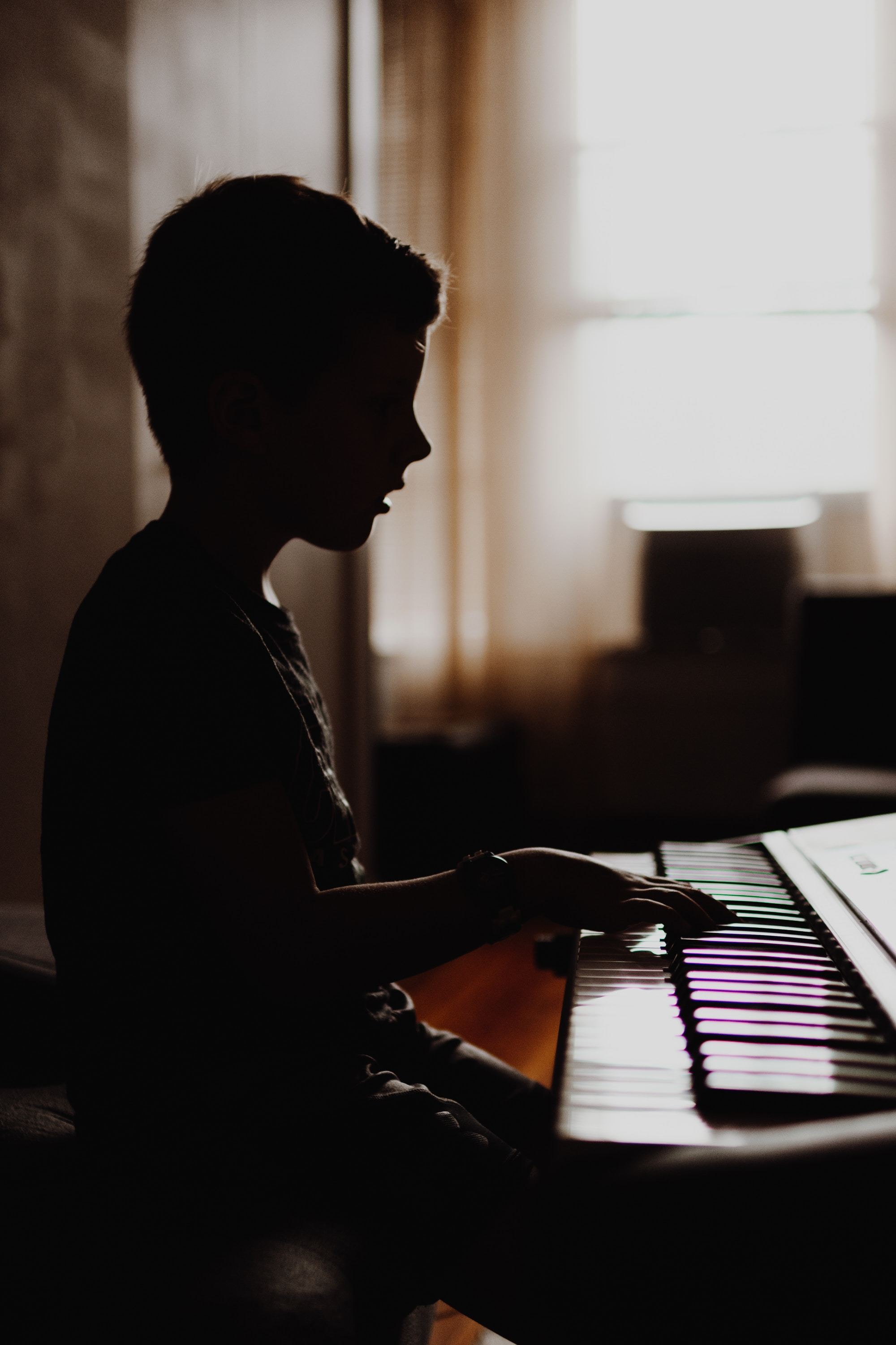Boy sits at electric piano, practicing his lessons.